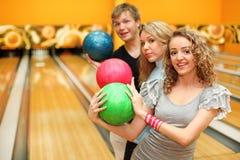 Bemannen Sie und zwei Mädchen, die Reihe der Kugeln im Bowlingspiel gebildet werden Lizenzfreie Stockbilder