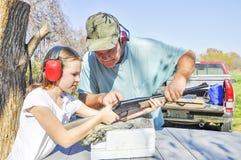 Bemannen Sie unterrichtendes Mädchen, wie man eine Feuerwaffe schießt stockfotos