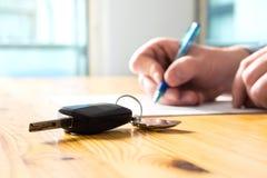 Bemannen Sie unterzeichnendes Autoversicherungsdokument oder mieten Sie Papier lizenzfreies stockfoto