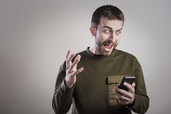 Bemannen Sie verärgertes an seinem Telefon, vergangen und erzürnt stockfotografie