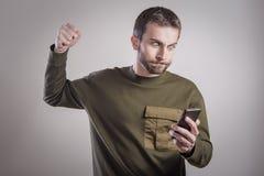 Bemannen Sie verärgertes an seinem Telefon, vergangen und erzürnt lizenzfreie stockfotos