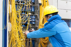 Bemannen Sie Verbindungsnetzkabel zu den Schaltern im Computerraum stockbild
