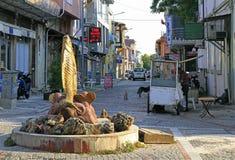 Bemannen Sie Verkauf etwas an den dekorativen Skulpturen, die Fische darstellen Lizenzfreie Stockfotografie