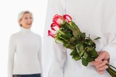 Bemannen Sie versteckenden Blumenstrauß von Rosen von der älteren Frau Stockbilder