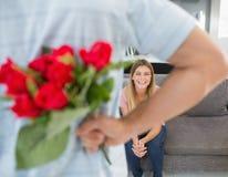 Bemannen Sie versteckenden Blumenstrauß von Rosen von der Freundin auf der Couch Lizenzfreies Stockfoto