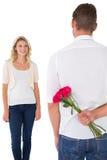 Bemannen Sie versteckenden Blumenstrauß von Rosen von der jungen Frau Lizenzfreie Stockbilder