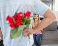 Bemannen Sie versteckenden Blumenstrauß von Rosen von lächelnder Freundin auf der Couch Stockfoto