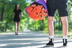 Bemannen Sie versteckendes Bündel rote Rosen hinter seinem zurück zu Überraschung sein Gi Lizenzfreie Stockfotos