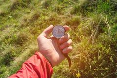 Bemannen Sie von Richtung mit einem Kompass in den Sommerbergen in der Hand suchen Standpunkt auf dem Hintergrund von grünen Hüge lizenzfreie stockfotos