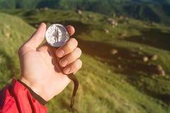 Bemannen Sie von Richtung mit einem Kompass in den Sommerbergen in der Hand suchen Standpunkt auf dem Hintergrund von grünen Hüge stockfoto