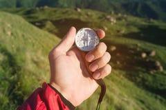 Bemannen Sie von Richtung mit einem Kompass in den Sommerbergen in der Hand suchen Standpunkt auf dem Hintergrund von grünen Hüge stockfotografie