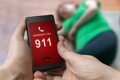 Bemannen Sie wählenden Notfall (Nr. 911) auf Smartphone Verletzte Frau stockfotografie