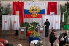 Bemannen Sie Würfe ein Stimmzettel in einer Urne in der Halle für die Abstimmung im russischen Hinterland Lizenzfreie Stockbilder