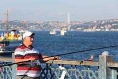 Bemannen Sie Würfe eine Angelrute von der Galata-Brücke Stockfoto