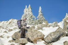 Bemannen Sie Wanderer mit dem Rucksack, der auf dem Weg auf großem Stein zur Gebirgsspitze am Winter steht Active macht Konzept i Stockbild