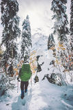 Bemannen Sie Wanderer mit dem Rucksack, der in schneebedeckten Wald des Winters reist Stockfoto