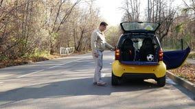 Bemannen Sie Wartehilfe nahe durch brocken Auto auf dem Waldweg stock video