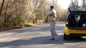 Bemannen Sie Wartehilfe nahe durch brocken Auto auf dem Waldweg stock video footage