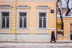 Bemannen Sie Weg auf Schneestraße nahe gelbem Gebäude in Moskau Lizenzfreie Stockfotos