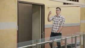 Bemannen Sie Weg entlang Halle in Geschäftszentrum sprechendem Smartphone stock video