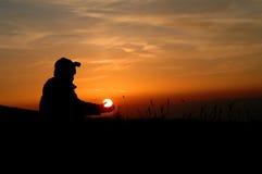 Bemannen Sie, wem die Sonne in seinen Händen anhält lizenzfreie stockfotos