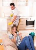 Bemannen Sie wischenden Boden während die Frau, die auf Sofa stillsteht Lizenzfreie Stockbilder