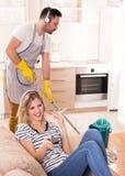 Bemannen Sie wischenden Boden während die Frau, die auf Sofa stillsteht Lizenzfreie Stockfotos