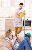 Bemannen Sie wischenden Boden während die Frau, die auf Sofa stillsteht Stockfotos