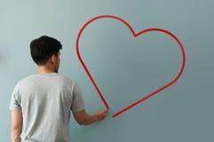 Bemannen Sie Zeichnungsherz für Valentinsgrußtag mit roter Kreide auf Wand Stockfoto