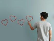 Bemannen Sie Zeichnungsherz für Valentinsgrußtag mit roter Kreide auf Wand Lizenzfreies Stockfoto