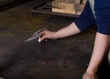 Bemannen Sie Zeichnungsprojekt des neuen Messers im Schmied auf der Metalltabelle Stockbild