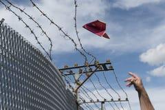 Bemannt die Hand, die seinen Pass wirft, der vorbei als Papierflugzeug gefaltet wird Stockbilder