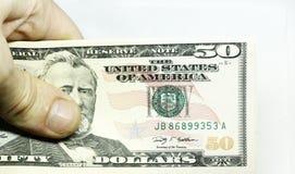 Bemannt die Hand, die Stapel der Papierdollar USA auf dem weißen Hintergrund hält Stockfotografie