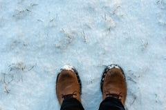 Bemannt Füße in den Winterstiefeln auf dem frischen Schnee stockfotos