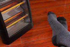 Bemannt Füße vor einer elektrischen Heizung lizenzfreie stockfotos
