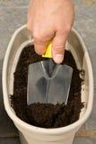 Bemannt Hand mit Grabungen eines Trowel in einem Pflanzer lizenzfreie stockfotos