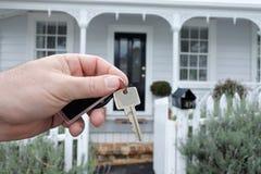 A bemannt Handgriffe ein Schlüssel gegen ein Haus in Auckland Neuseeland Lizenzfreies Stockfoto