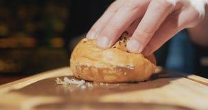 Bemant de hamburgerbroodje van handenbesnoeiingen met sesamzaden in de twee helften op houten raads dichte omhooggaand Langzame M stock videobeelden