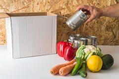 Bemant de schenkings lege doos met voedsel dichtbij de doos en hand stock foto