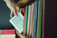 Bemant hand krijgt ebook onder oude boeken van het boekenrek nieuwe tec Royalty-vrije Stock Afbeeldingen