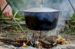 A bemant hand ontsteekt een brand onder een pan, die zich op een brand bevindt royalty-vrije stock foto