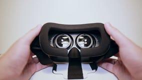 Bemant handen nemen virtuele werkelijkheidsglazen, vr en dragen hen, witte achtergrond