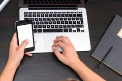 Bemant handen typend op slimme telefoon terwijl het werken aan laptop gegevens verwerken stock foto