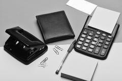 Bemant leerportefeuille en kantoorbehoeften Calculator, gatenstempel, adreskaartje, notadocument, pen en klemmen Zaken en het wer stock fotografie