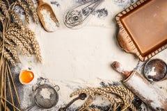 Bemehlen Sie Backenhintergrund mit rohem Ei, Nudelholz, Weizenähre und rustikal backen Sie Wanne Stockbilder