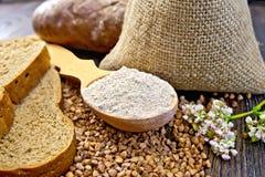 Bemehlen Sie Buchweizen im Löffel mit Getreide und Brot an Bord Lizenzfreies Stockfoto