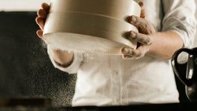Bemehlen Sie Sieb in den männlichen Chefhänden in der Küche lizenzfreie stockfotos