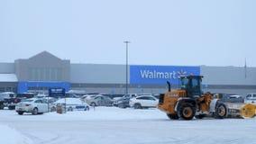 BEMIDJI, MANGANESO - 27 DE DICIEMBRE DE 2018: Máquina de la retirada de la nieve que despeja el estacionamiento de Walmart metrajes