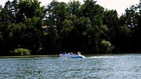 Bemidji, Minnesota - 4 de julho: Barco de motor desportivo do runabout com passageiros felizes filme