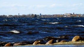 Bemidji, Minnesota se ve a través del lago Irving como ondas que hacen espuma rueda sobre orilla metrajes